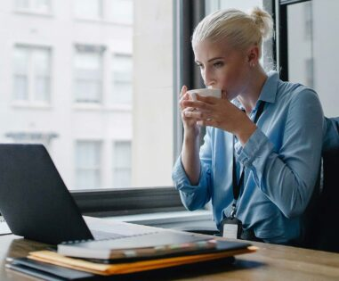 Woman drinking coffee while working digitally